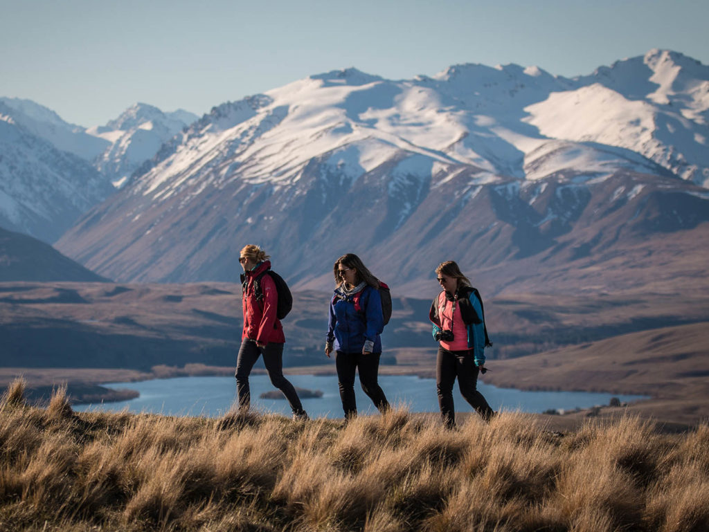 Three hikers on the Richmond Trail Tekapo with lake and snowy mountains in background